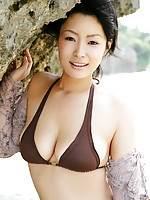 Seductive asian babe with small perky breasts in a pink bikini