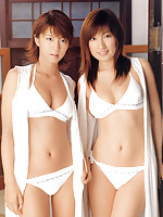 Two sensuous asian babes posing together in their white bikinis