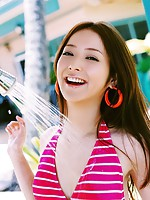 Long haired asian cutie having fun in a striped hot pink bikini