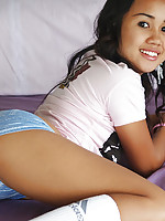 Shy Asian teen in pink t-shirt shows little blue panties