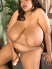 Big black woman plays with her white dildo