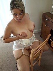 Curvaceous buxom housewife in basque and tan nylons shows off her cunt