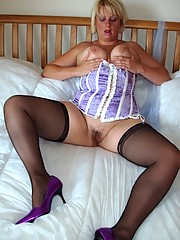 Milf in basque and stockings dildo fucks herself on bed