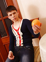 Sexy boy plays with an orange while stripping off