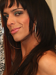 Vivy Aguilera is a beautiful brunette transsexual from Porto Alegre. She has a long, slender body and an even longer cock. While wearing stiletto boots and fishnet stockings, she spreads her legs on the bed and shows off her tight she-pussy.