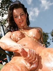 Brunette shemale with big tits stripping in the park