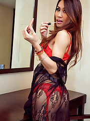 Sultry t-girl Nan in red lingerie applies make-up