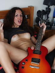 Sweet TS babe posing her goodies in bed with a guitar
