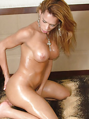 Horny shemale strips and oils up her thick shecock