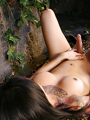 Brunette beauty Neveah strips in the jungle
