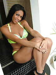 Shemale in a green bikini shows her nice tits