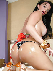 Horny brunette shemale has Oiled up big ass titties and a thick shecock