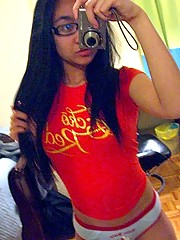 Cute Asian teen with glasses taking selfpics