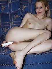 Skinny chick plays with her dildo on the couch