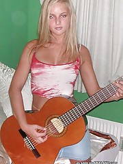 Blonde rockstar cutie posing with her guitar