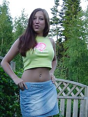 Sexy brunette cutie wearing a mini skirt posing in the garden