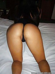 Shy Asian chick posing with her ass in a tiny thong