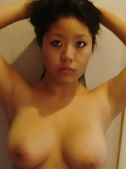 Busty topless Asian holding her round tits