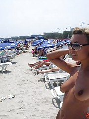 Steamy hot naughty MILF goes topless in a beach